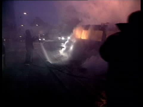 Gv's Overturned van burning and Police van and vandalised police van behind GV residential street and van on fire ZOOM IN van as fire blazes FRONT...