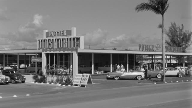 vidéos et rushes de 1955 ws pan oldsmobile car dealership / detroit, michigan - 1955