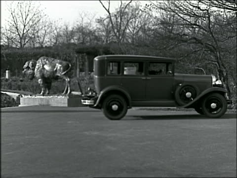 b/w 1928 oldsmobile parks in parking lot; two women get out - 1928 stock-videos und b-roll-filmmaterial