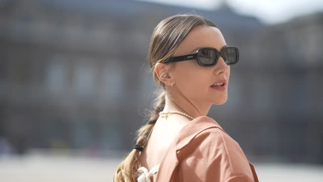 olesya senchenko wears a white pearls necklace, a gold chain necklace, earrings, a pale orange blazer jacket oversized dress, a black bra underwear,... - braided hair stock videos & royalty-free footage