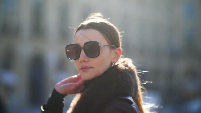 olesya senchenko wears sunglasses from dior, a brown leather long winter coat with fluffy collar from nour hammour, a black wool turtleneck pullover... - ponytail stock videos & royalty-free footage