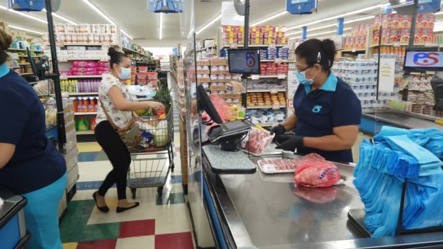 olga jiminez stands behind a partial protective plastic screen and wears a mask and gloves as she works as a cashier at the presidente supermarket on... - cashier stock videos & royalty-free footage