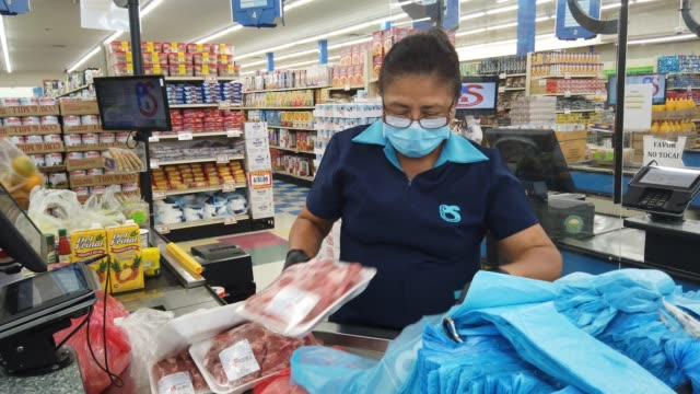 vidéos et rushes de olga jiminez stands behind a partial protective plastic screen and wears a mask and gloves as she works as a cashier at the presidente supermarket on... - denrée périssable