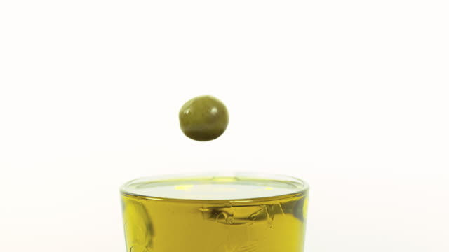 Olive falling into Olive Oil against White Background, Slow Motion 4K