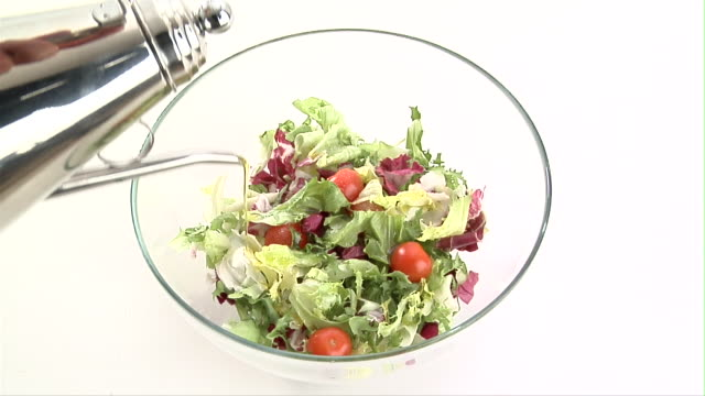 CU, HA, Olive oil being poured into salad in bowl