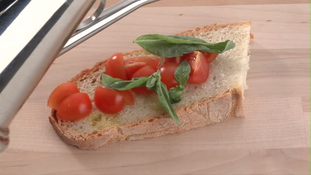 CU, Olive oil being poured on slice of bread with tomatoes and basil