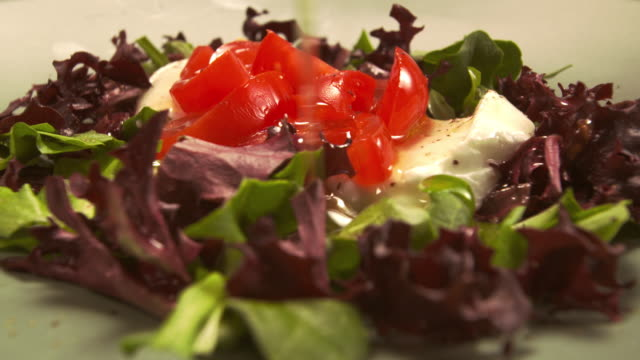 ms ds olive oil being poured over mozzarella and tomato salad on bed of greens / los angeles, california, united states - salad oil stock videos & royalty-free footage