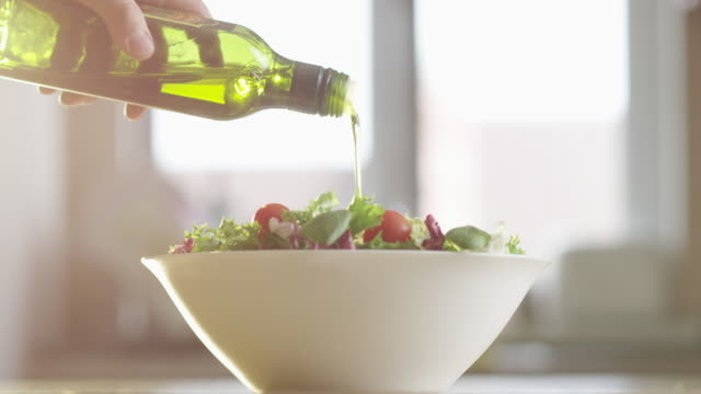 olive oil is pouring into a plate of vegetable salad with lettuce and cherry tomatoes  on a kitchen table with sun flares - サラダ点の映像素材/bロール