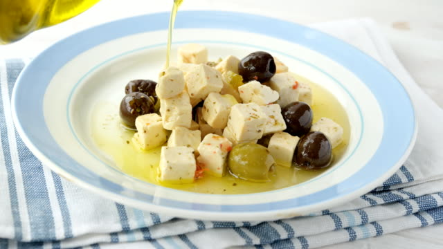 olive oil pouring on feta cheese and olives - シェーブルチーズ点の映像素材/bロール