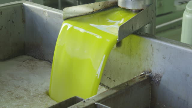 CU olive oil streaming from the press into a retaining basin RED R3D 4K
