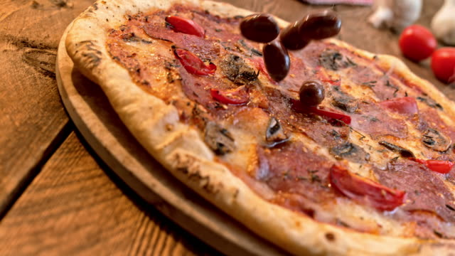 slo mo pan olives falling onto a salami pizza - black olive stock videos & royalty-free footage