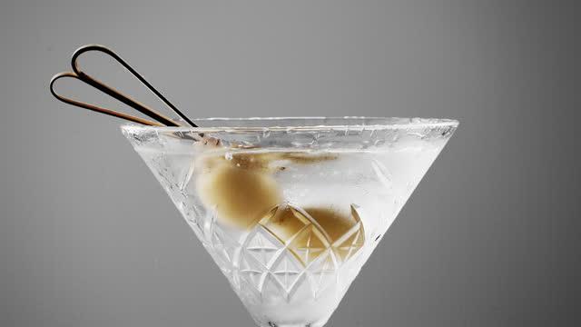 oliven garnieren spritzen in martini aus nächster nähe - dry stock-videos und b-roll-filmmaterial