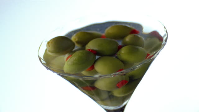 cu olives in spinning martini glass - martini glass stock videos & royalty-free footage