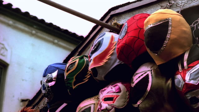 vidéos et rushes de zi olvera street vendor's display of mexican wrestling masks hanging on the booth pediment, with some unnatural coloring and a spanish architecture building beyond / los angeles, california, united states - procédé croisé