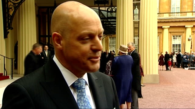 olympians interviewed after recieving honours; england: london: buckingham palace: ext sir dave brailsford cbe chatting / brailsford shows his medal... - roswell stock videos & royalty-free footage
