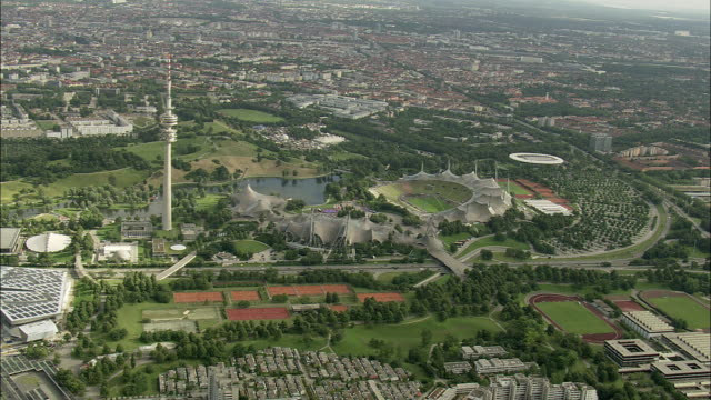 AERIAL. Olympiapark and communication tower with cityscape in background, Munich, Bavaria, Germany