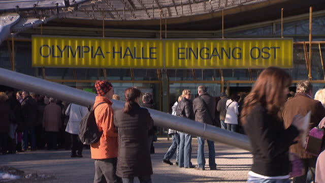 Olympiapark,  Olympiahalle, Holiday On Ice, audience, people on entrance, roof of Olympiahalle, panning shot, blue sky