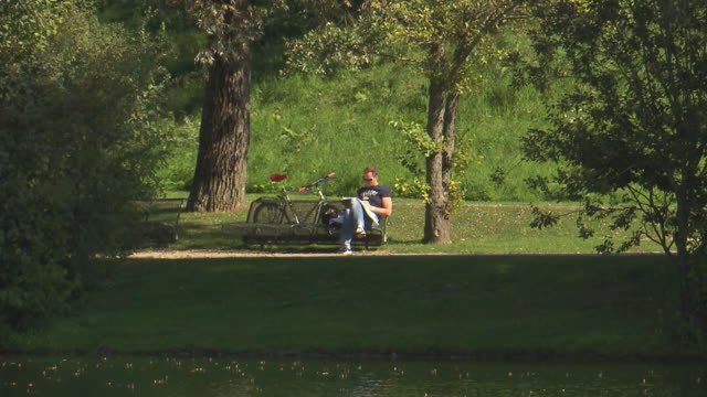 Olympiapark,  Park, Olympiasee, lake, water, man sitting on a bench, bike, lawn, trees, sunny
