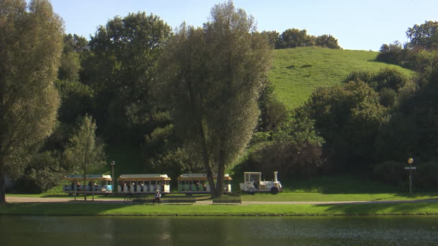 Olympiapark,  Park, Olympiasee, lake, water, man sitting on a bench,, lawn, trees, sunny, sightseeing train drive through