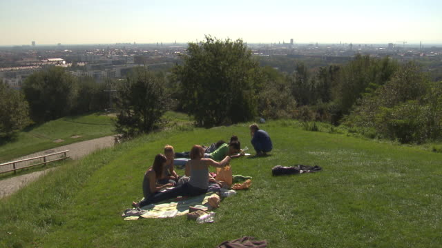 Olympiapark,  Park, skyline of Munich, people sitting on a hill, lwan, trees, blue sky, Frauenkirche in background