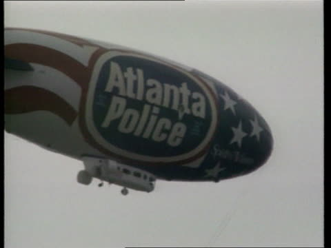 olympic bomb; itn usa: georgia: atlanta: ext seq group of police motorcyclists towards & past with sirens sot; blimp in sky with 'atlanta police' on... - personal land vehicle stock videos & royalty-free footage