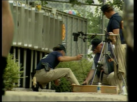 vidéos et rushes de georgia: atlanta: day seq fbi officers gathering evidence from the area surrounding the public telephone used to phone in the bomb warning - bombe