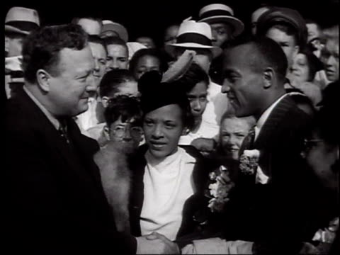 Olympic champion Jesse Owens returns home and is greeted by huge crowd / Owens with wife Ruth Solomon / He's welcomed at the station by the Mayor and...