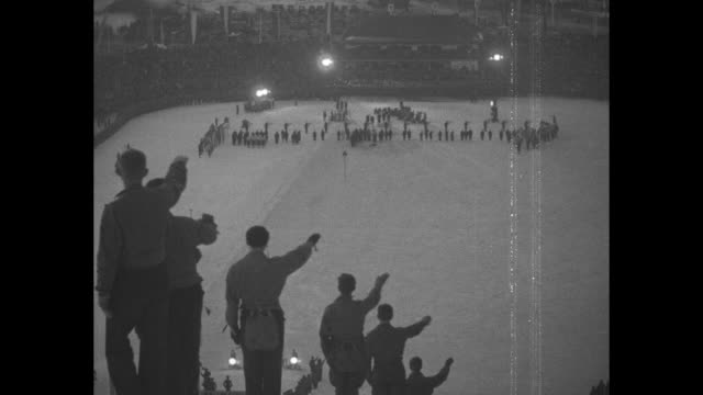 Olympic flame tower at 1936 Winter Olympics in GarmischPartenkirchen Germany / photographers kneel for pictures of medal presentation at end of ski...