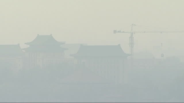 olympic games preparations: pollution fears: olympic stadium; china: beijing: ext brids nest stadium - built for the 2008 olympic games - obscured by... - 2008年北京夏季オリンピック点の映像素材/bロール