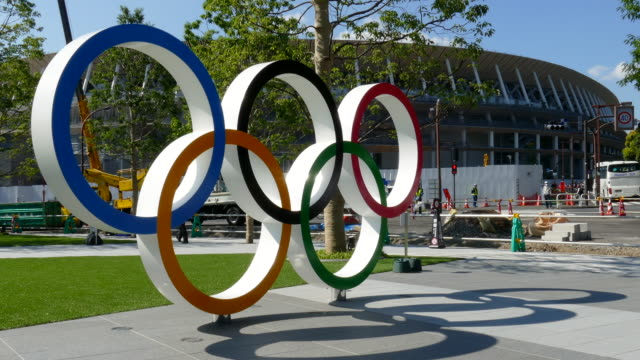 olympic rings are seen near to the new national stadium under construction which the completion date is set for late november on june 13 tokyo japan... - olympic rings stock videos & royalty-free footage