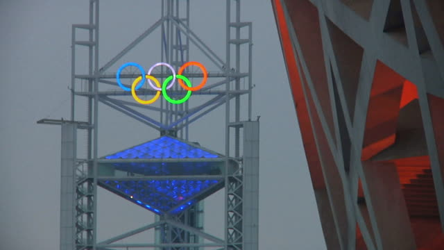 ws olympic rings on tower with detail of bird's nest olympic stadium in foreground / beijing, china - the olympic games stock videos & royalty-free footage