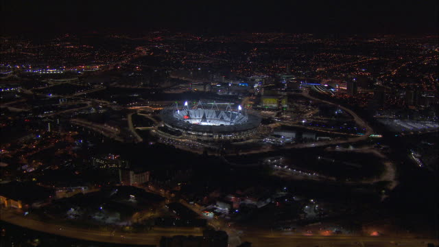stockvideo's en b-roll-footage met olympic stadium glows in olympic park at night in london, england. - london england