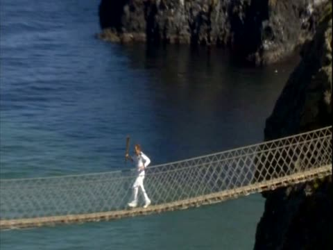 olympic torchbearer runs over carrick-a-rede rope bridge, a suspension bridge in northern ireland - suspension bridge stock videos & royalty-free footage