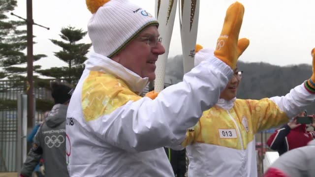 olympics chief thomas bach takes part in the torch relay ahead of the opening ceremony of the 2018 winter games in pyeongchang - olympic torch stock videos & royalty-free footage