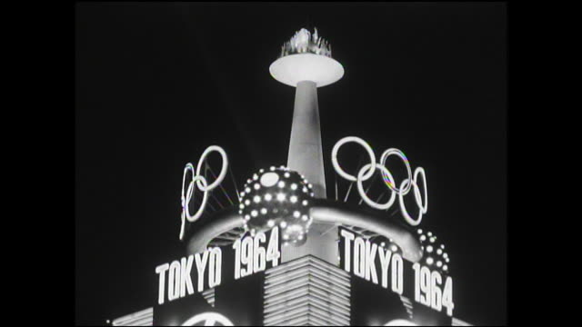 vídeos de stock e filmes b-roll de a 1964 olympics sign is one of many lights that illuminate buildings on a busy ginza street. - 1964