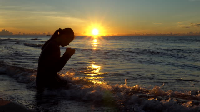 oman praying on beautiful sunset background - christianity stock videos & royalty-free footage