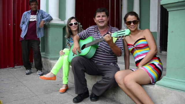 omar ramón mirabal jiménez alias 'el muneco' is a popular character that wonders the streets of santa clara city playing his acoustic guitar and... - plucking an instrument stock videos & royalty-free footage