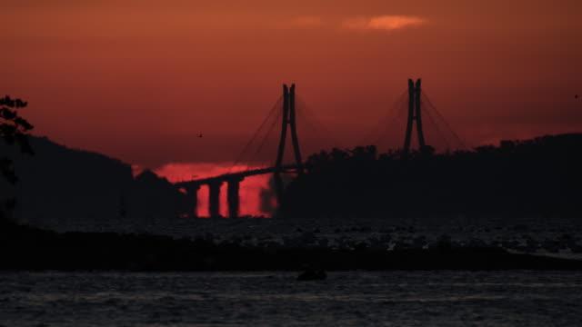 omega sunrise of geogadaegyo bridge (busan-geoje bridge) / gyeongsangnam-do, south korea - omega sun mirage stock videos & royalty-free footage