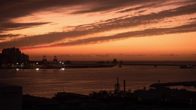 omega sunrise over fishing vessels at sinseondae pier / nam-gu, busan, south korea - omega sun mirage stock videos & royalty-free footage