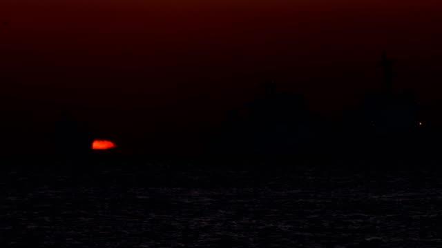 omega-shaped sunrise over fishing boats and freighters around saengdo island (kettle island) / yeongdo-gu, busan, south korea - omega sun mirage stock videos & royalty-free footage