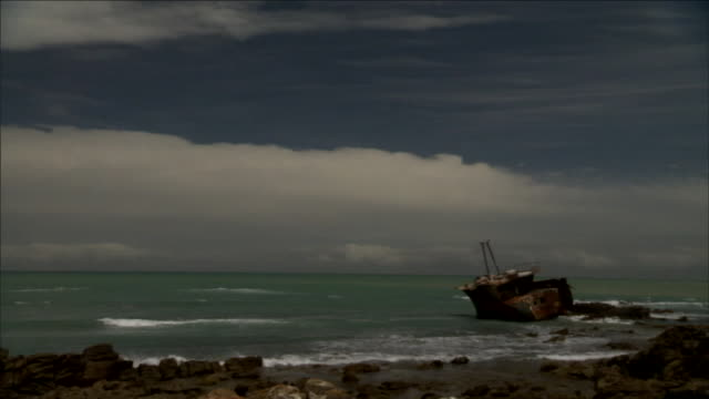 ominous storm clouds loom above a ship that has run aground. - shipwreck stock videos & royalty-free footage