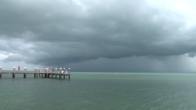 Ominous storm clouds signaling an approaching severe thunderstorm move towards Marathon FL as people watch from a dock