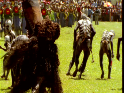 Omo Masalai skeleton dancers shake their posteriors at character in costume as they perform at Mount Hagen show, Papua New Guinea