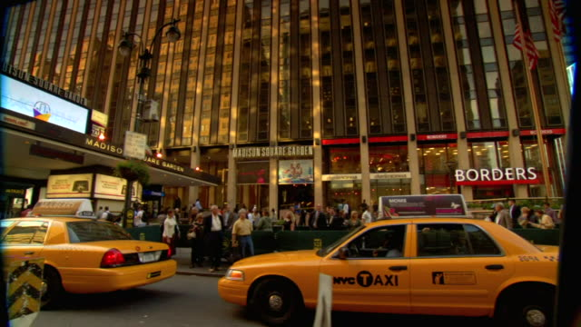 stockvideo's en b-roll-footage met on 7th avenue unidentifiable people crowded on street in front of penn station building traffic including taxi cabs parked nypd police vans nyc - new york city penn station