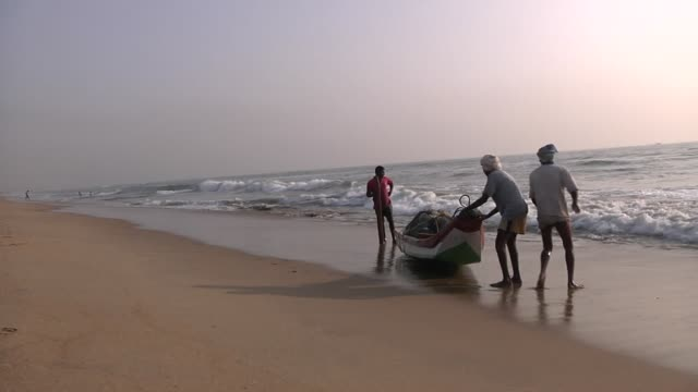 on a beautiful morning shots include wide shots of marina beach chennai with boats coming towards the beach and travelling across shot fisherman... - chennai stock videos & royalty-free footage