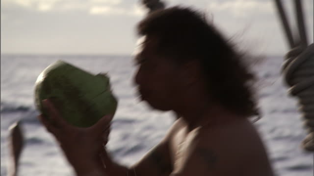 vídeos y material grabado en eventos de stock de on a boat, a polynesian man drinks from a hollowed-out gourd before handing it to a second man who also drinks. - sediento