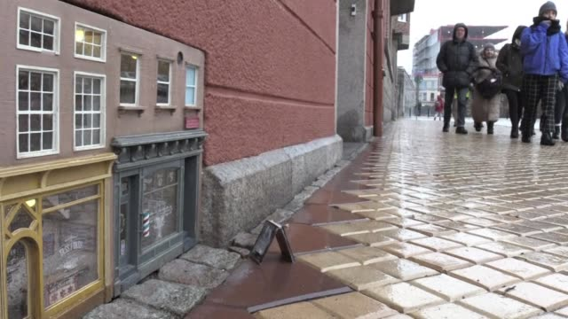 On a building on a street in Malmo in Sweden built into the air vent at pavement level are two little pastel coloured storefronts that would fit into...