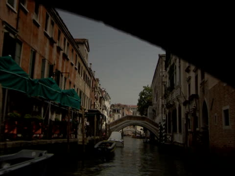 pov on a canal boat navigating through narrow canal under bridges, venice, italy (sound available) - spira tornspira bildbanksvideor och videomaterial från bakom kulisserna