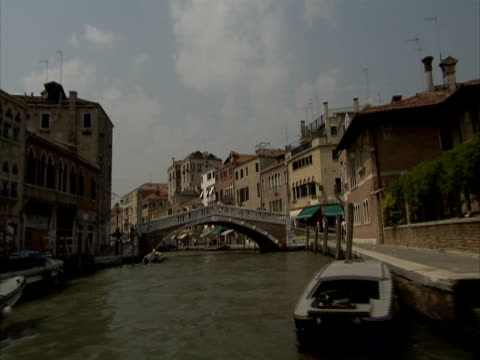pov, on a canal boat navigating through narrow canal under bridges, venice, italy (sound available) - spira tornspira bildbanksvideor och videomaterial från bakom kulisserna