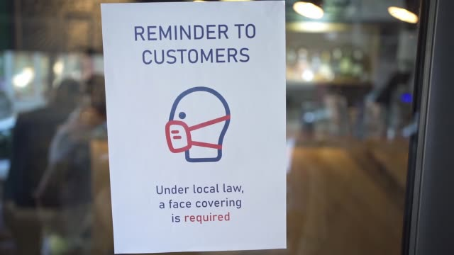 on a coffee shop door their is a information sign to customers that wearing protectiv face mask is obligation at this coffee shop during covid-19 pandemic - information sign stock videos & royalty-free footage